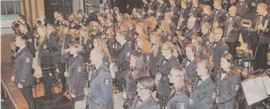 Foto des Orchesters, Dirigent Andreas Reuber vorne stehend.
